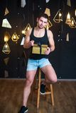 Handsome man in black tank top holds a gift in her hands, opens. Handsome young man posing in studio, model photo. holds a gift in his hands, opens a gift, a Royalty Free Stock Photography