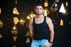 Handsome man in black tank top, posing, fashion portrait. Handsome young man posing in studio, model photo. holds a gift in his hands, opens a gift, a surprise Royalty Free Stock Photos