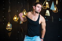 Handsome man in black tank top, posing, fashion portrait. Handsome young man posing in studio, model photo. holds a gift in his hands, opens a gift, a surprise Royalty Free Stock Photography