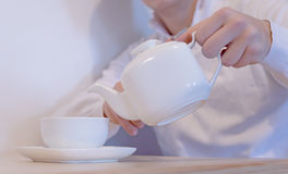 Handsome young man pouring tea in cup Royalty Free Stock Photography