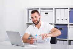 Handsome young man pouring water into a glass Stock Photography
