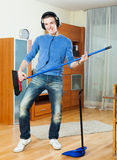Handsome young man pretending to play guitar with broom. Handsome happy young man pretending to play guitar with broom in living room at home Royalty Free Stock Photography