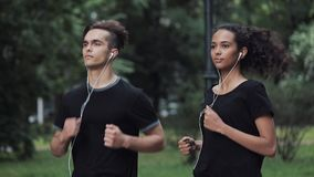 Handsome Young Man and Pretty Mousline Girl in Headphones Looking Relaxed Running in Park Side view. Handsome Young Man and Pretty Mousline Girl in Headphones stock video footage