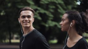Handsome young man and pretty mousline girl in headphones looking relaxed running in park side view close up girl on the stock footage