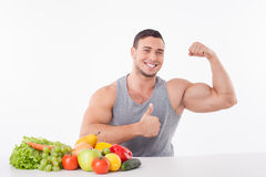 Handsome young man is proud of his healthy body. Cheerful guy is sitting at the table near fruits and vegetables. He is flexing his bicep and giving thumb up Royalty Free Stock Images