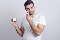 Handsome young man putting face cream Stock Images