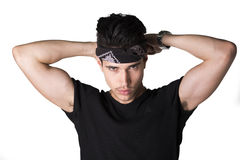 Handsome young man putting on headband Stock Photo