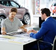 Handsome young man reading a booklet at the dealership  showroom. Stock Photography