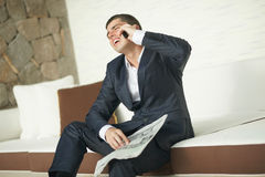 Handsome young man reading morning newspaper in black suit. Royalty Free Stock Photography