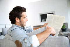 Handsome young man reading newspaper Royalty Free Stock Images