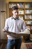Handsome young man reading newspaper at home Stock Photo