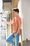Handsome young man reading text message on cell phone Stock Photo