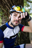 Handsome young man relaxing after cycling in the mountain. Stock Photos