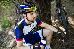 Handsome young man relaxing after cycling in the mountain. Royalty Free Stock Image