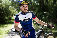 Handsome young man relaxing after cycling in the mountain. Stock Images