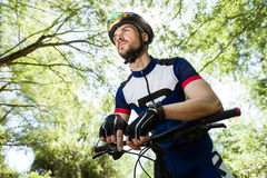 Handsome young man relaxing after cycling in the mountain. Stock Image