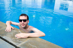 Handsome young man relaxing in the swimming pool Royalty Free Stock Images
