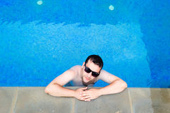 Handsome young man relaxing in the swimming pool Royalty Free Stock Photography