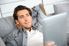 Handsome young man relaxing with  tablet on sofa Stock Image