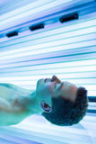 Handsome young man relaxing  in a modern solarium Stock Photos