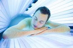 Handsome young man relaxing during a tanning session Stock Images