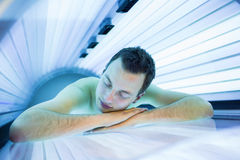 Handsome young man relaxing during a tanning session Royalty Free Stock Photos