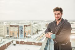 Handsome young man relaxing on winter snowy terrace after getting steamed bath. Cheerful adult man reaxing on terrace and wearing bathrobe. He is holding a cup royalty free stock photography