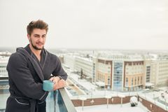 Handsome young man relaxing on winter snowy terrace after getting steamed bath. Holding a cup of coffee in his hands, posing against snowy winter city stock photography