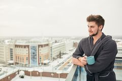 Handsome young man relaxing on winter snowy terrace after getting steamed bath. Holding a cup of coffee in his hands, posing against snowy winter city stock photo