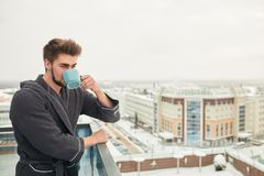 Handsome young man relaxing on winter snowy terrace after getting steamed bath. Healthy bearded caucasian man drinking hot tea, looking at winter cold frosty stock image