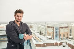 Handsome young man relaxing on winter snowy terrace after getting steamed bath. Healthy bearded caucasian man drinking hot tea, looking at winter cold frosty stock photo