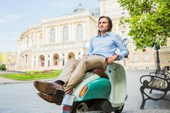 Handsome young man resting on scooter Stock Photography