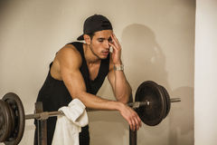 Handsome young man resting after workout in gym Stock Photo