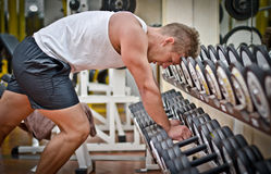 Handsome young man resting after workout in gym. Handsome young athletic man resting on dumbells rack after workout in gym Royalty Free Stock Photography