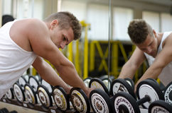 Handsome young man resting after workout in gym. Handsome young athletic man resting on dumbells rack after workout in gym Stock Images
