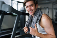 Handsome young man resting after workout with towel around his neck Royalty Free Stock Photography