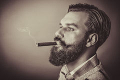 Handsome young man with retro look smoking a cigar Stock Photography