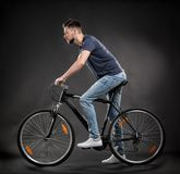 Handsome young man riding bicycle. On dark background Stock Images
