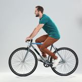 Handsome young man riding bicycle. On light background Stock Photography