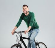 Handsome young man riding bicycle. On light background Stock Images
