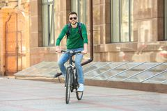 Handsome young man riding bicycle. Outdoors Stock Image