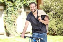 Handsome young man riding bicycle outdoors. On sunny day Stock Image