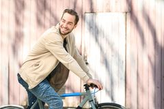 Handsome young man riding bicycle outdoors. On sunny day Stock Images