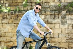 Handsome young man riding bicycle outdoors. On sunny day Stock Photos