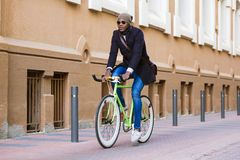 Handsome young man riding a bike in the street. Portrait of handsome young man riding a bike in the street Stock Photo