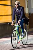 Handsome young man riding a bike in the street. Portrait of handsome young man riding a bike in the street Royalty Free Stock Image