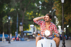 Handsome young man riding  a vintage scooter Stock Images
