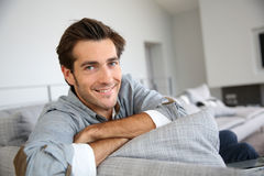 Handsome young man rlaxing on sofa Stock Image