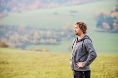 Handsome young man running outside in autumn nature, resting Royalty Free Stock Photos