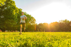 A handsome young man running during sunset in a park Stock Image